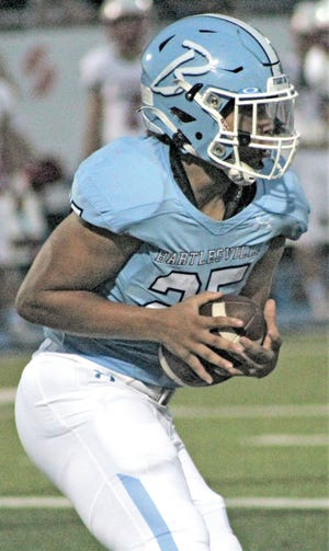 Jalen Colston carries the ball Friday night for the Bartlesville High football team..