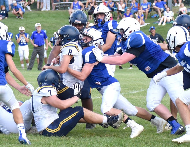 Dolgeville defender Cameron Dager stands up Notre Dame quarterback Chris Kelly (8) at the line of scrimmage and gets a push from teammate Elijah Morse (right) on a fourth down stop during the first quarter of Saturday's game.