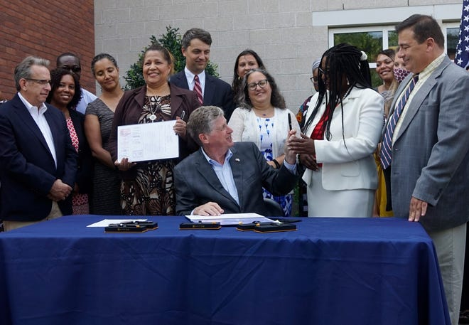 Gov. Dan McKee hands a ceremonial pen to Rep. Marcia Ranglin-Vassell after signing a new doula bill last month. But the daily schedules of McKee, and his gubernatorial challengers, go well beyond ceremonial signings and photo ops.