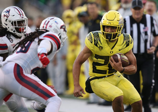 Oregon's Travis Dye, right, runs against Stony Brook during the second half.