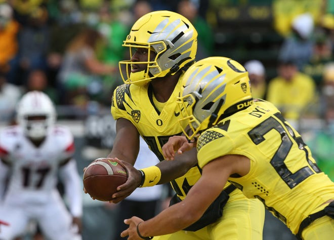 Oregon quarterback Anthony Brown Jr., left, hands the ball off to Travis Dye during the second quarter against Stony Brook.