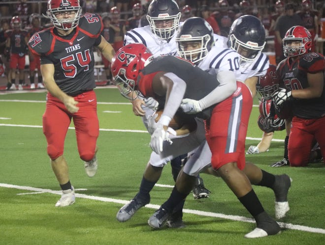 Shawnee's Jamir Owens (10) attempts to wrap up the Carl Albert ball carrier as Samuel Anderson (44) and another unidentified Shawnee player pursue on the play Friday night at Carl Albert.
