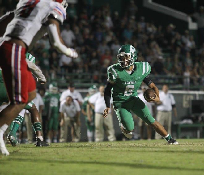 Seminole quarterback Brendan Rodriquez (8) runs with the football Friday night against Evangel Christian.