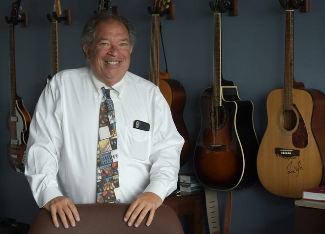 Worcester Red Sox President Dr. Charles Steinberg stands in front of some of the guitars hanging on the wall in his private box at Polar Park.