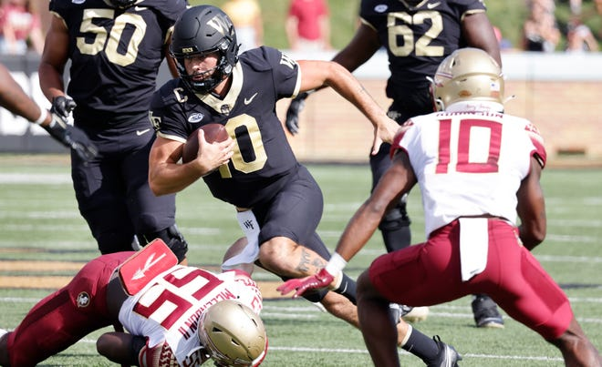 Sep 18, 2021; Winston-Salem, North Carolina, USA; Wake Forest Demon Deacons quarterback Sam Hartman (10) runs the ball for a first down between Florida State Seminoles defensive back Jammie Robinson (10) and defensive end Derrick McLendon II (55) during the first quarter at Truist Field.