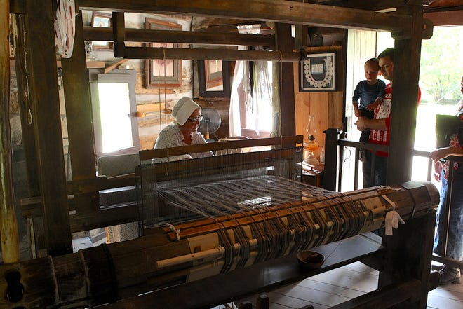 Karen Marsh weaves rag rugs with a weaving loom in the Spring Mill Village Weaver's Shop Saturday. Marsh said the loom was built by a man named George Sheeks, who moved to the area in 1816. The activity was part of the annual Mitchell Tri Kappa Spring Mill Village Candlelight Tour.