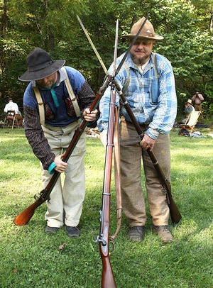 """Brian Stevens, left, and Bret Stewart construct a """"stack"""" comprised of civil war era muskets. The two were part of a Civil War reenactment contingent near the Blacksmith Shop in Spring Mill Village Saturday."""