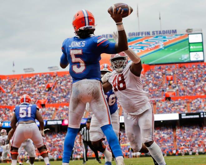 Florida quarterback Emory Jones throws under heavy pressure from Alabama defensive lineman Phidarian Mathis (48) during Saturday's game at Ben Hill Griffin Stadium.