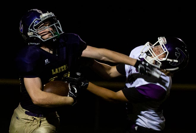 Millersport's Cody Blosser (19) stiff arms a Miller defender as the Lakers hosted the Miller Falcons in high school football action at Millersport High School in Millersport, Ohio on September 28, 2021. This was the first home football game that was held in the stadium in four years.