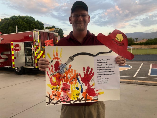 """Jason Inman displays one of the pieces of art he collected from students at Carter Elementary School on Friday, Sept. 17, 2021, in Palm Desert, Calif. That evening, the Parent-Teacher Organization held a """"drive-thru"""" meet and greet event, and Cal Fire firefighters participated to greet the children."""