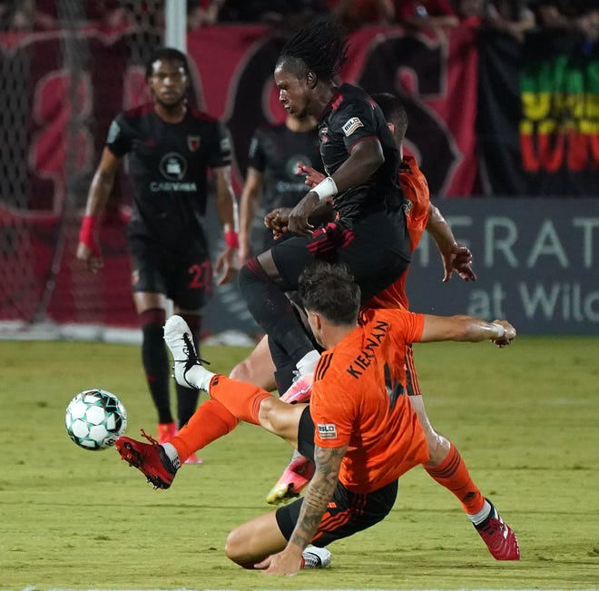 Phoenix Rising's Darren Mattocks fights a double-team from Orange County Dekel Keinan and an unidentifiable player  in the first half at the Phoenix Rising Soccer Complex in Chandler Sept, 18, 2021.