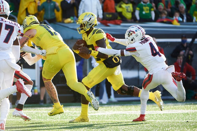 Sep 18, 2021; Eugene, Oregon, USA; Oregon Ducks quarterback Anthony Brown (13) breaks away from Stony Brook Seawolves defensive back Gregory Young II (4) for a touchdown during the first half at Autzen Stadium. Mandatory Credit: Troy Wayrynen-USA TODAY Sports