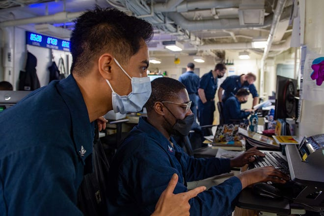 Personnel Specialist 3rd Class Joshua Dadiuas, left, a native of Los Angeles, and Personnel Specialist 3rd Class Trayvon Robinson, a native of Tallahassee, Florida, audit pay entitlements in the personnel office aboard Nimitz-class aircraft carrier USS Carl Vinson (CVN 70) in the South China Sea on Sept. 6, 2021.