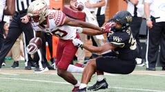 Demon Deacons linebacker Joshua Sosanya tackles Seminoles wide receiver Ontaria Wilson.