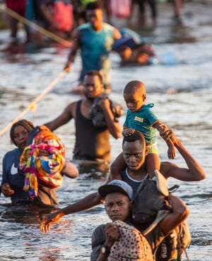 Haitian migrants cross the Rio Grande river into Ciudad Acuna from Del Rio, Texas as they decide to leave the migrant encampment underneath the Del Rio International Bridge after concerns of food scarcity and deportations to Haiti on Monday Sept. 20, 2021.