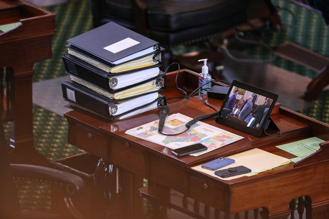 A Senate desk sits cluttered with phones, maps, and a stack of binders. The Texas Senate met for the start of a new special session on Sept. 20. [AMERICAN-STATESMAN/FILE]