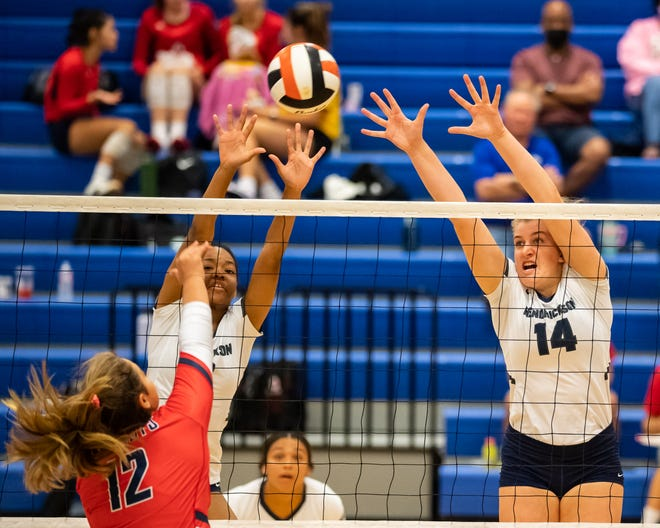 Karys Dove, left, and Ella Wendel go up for a block for Hendrickson against Maissa Pozo of East View in a match earlier this season. The pair helped the No. 6 Hawks defeat rival Pflugerville Friday.