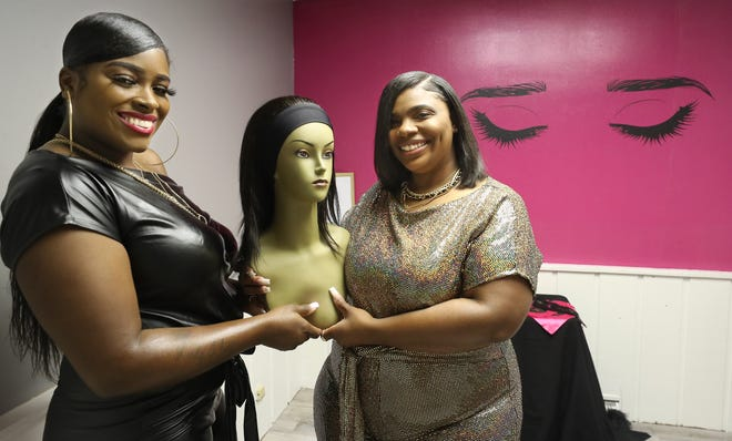 Tierra Brown of The Wig Hive and Denise Watkins of Diamond District hold a mannequin with a wig in the eyebrow room of their new combined shop in Tallmadge.