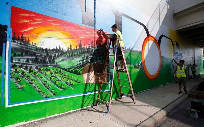 Nordonia High School students Cameron Elliott, 17, standing on the ladder, Nicholas Nguyen, 18, and Paige Sobczyk, 17, paint a mural Saturday on the wall of the state Route. 82 overpass in Macedonia.