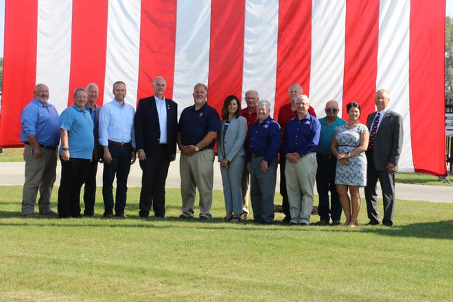 Firelands Electric Cooperative's trustees and staff stand with local legislators in front of an American flag provided by the Northern Ohio Fraternal Order of the Leatherheads Society during the recent ACRE Co-op Owners for Political Action event. Standing, from left, are Firelands' trustees Tom Lucha, Kevin Reidy and Dan Schloemer; Ohio Sen. Nathan Manning, Ohio Rep. Dick Stein, Ohio Rep. Darrell Kick, and Ohio Rep. Marilyn John; Trustees Gene Lamoreaux, John Martin, Bruce Leimbach, Rob Turk and Carl Ayers; Ohio Electric Cooperative's Government Affairs Coordinator Kelly Barr; and Firelands' General Manager Dan McNaull.