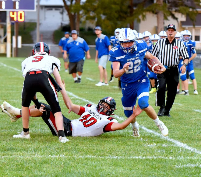 Collins-Maxwell's Brody Sampson runs by Dunkerton's Kaden Behrens (40) and Dylan Marquart during the Spartans' 62-50 loss to the Raiders on homecoming night in Maxwell Friday. It was the Spartans' final game on the old Maxwell field.