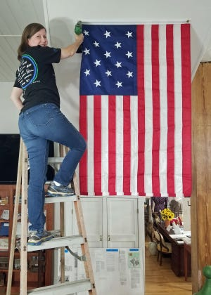 Jefferson County Historical Society member Kerri Shoemaker of Wadley finishes securing the museum's new 15-star, 15-stripe historical American flag.  Adopted on May 1, 1795, with the statehoods of Kentucky and Vermont, this is the only official American flag with more than 13 stripes.  This flag would have flown above the state capitol building in Louisville. As Jefferson County celebrates its 225th Anniversary, and the 25th Anniversary of the Historical Society, the museum building is undergoing repairs and upgrades, including a new commercial fire and security alarm system.  Located at 112 W Broad Street in downtown Louisville, the museum is open on Tuesdays from 1 p.m. to 5 p.m., and on Thursdays from 5 p.m. to 8 p.m. Admission is free.