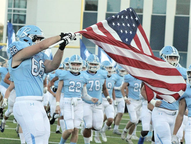 Bartlesville High School senior Ridge Brewington, No. 66, displays the American flag as the Bruins charge onto the field last Friday evening at Custer Stadium.