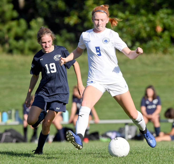 Julietta Marzot  of Falmouth Academy prepares to pass under pressure from Olivia Daigle of Cape Cod Academy on Monday.