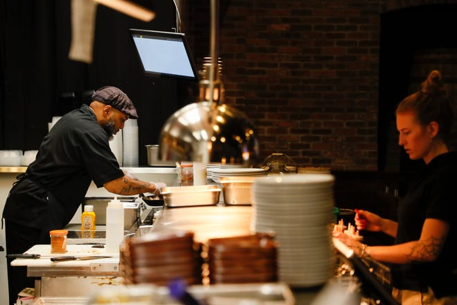 Chef Cartell Raysor, left, prepares food while working at Barrel and Boar in Westerville. The restaurant had to increase their prices because of the increase in the price of food, especially meat.