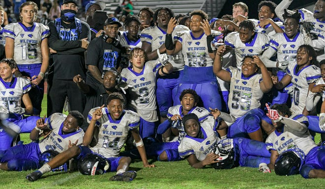 The Wildwood Wildcats celebrate after beating South Sumter 20-9 in Bushnell. It was Wildwood's first regular-season victory at South Sumter since a 31-16 victory in 1990. [PAUL RYAN / CORRESPONDENT]