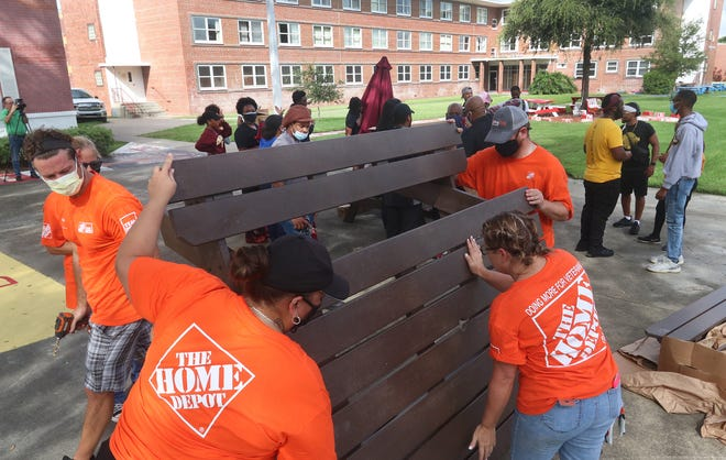 Home Depot employees set a picnic table up, Monday September 20, 2021 during a campus improvement project with Bethune Cookman University students.