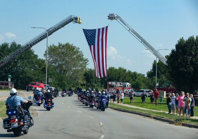 Independence fire trucks hold aloft a United States flag Saturday over Jackson Drive as a motorcade of officers escorted the body of Officer Blaize Madrid-Evans from Centerpoint Medical Center to the Jackson County medical examiner's office, following organ donation procedures. One of Madrid-Evans' kidneys went to an injured police officer in Springfield, Missouri.