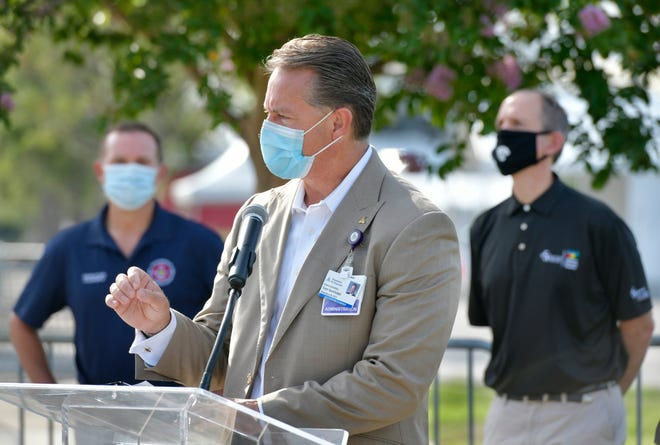 Tom VanOsdol, president and CEO of Ascension St. Vincent's, speaks during a news conference about hospital safety amid the coronavirus pandemic with Mayor Lenny Curry (left) and then-Baptist Health President and CEO Brett McClung in May 2020 at a coronavirus testing site at TIAA Bank Field in Jacksonville.