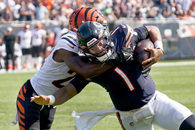 Chicago Bears quarterback Justin Fields (1) carries the ball and is tackled by Cincinnati Bengals cornerback Chidobe Awuzie during the second half of a Sunday's game in Chicago.