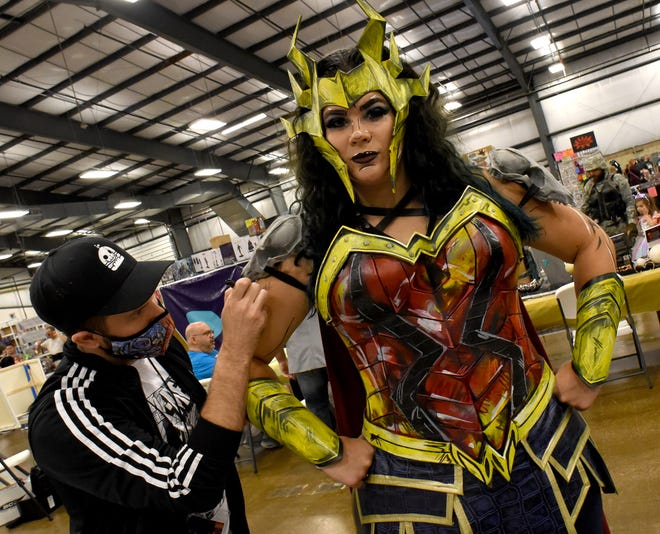 Death Metal Wonder Women (Katie Whittaker) of the The League of Enchantment has a few final touches painted on by artist and designer Kyle RISE Irving at the Monroe Pop Fest Saturday.