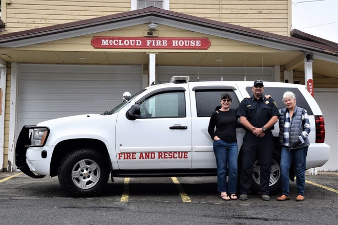 McCloud community members Shannon Reyna and Sarah Kidd stand with McCloud Fire Department Assistant Chief Trenton Vogus in front of the 2008 Chevy Tahoe administrative vehicle that was bought for the department with the money they raised.