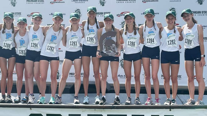 Petoskey's girls cross country runners stand with the championship trophy of the Bronze Division of the Spartan Invite from Friday.