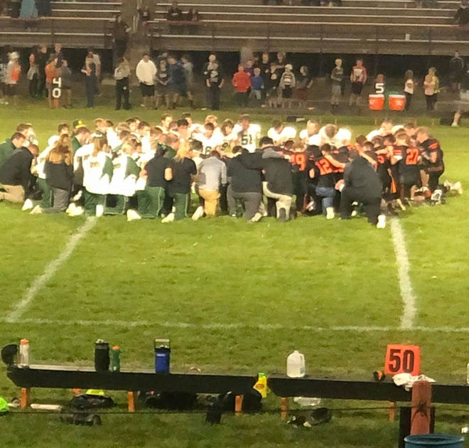 St. Mary's Knights prayed with the Madelia Blackhawks following an injury to a Blackhawk player Friday, Sept. 17.