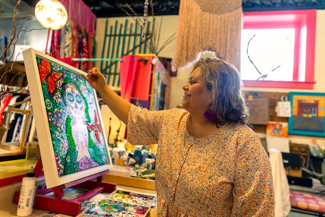 Monica Zanetti, the owner of Wild Rose, works on a painting of La Catrina at her artisan boutique in downtown Springfield on Monday. La Catrina is one of the most recognizable symbols of The Day of the Dead celebrations. Wild Rose features the work of artists from central Illinois. [Justin L. Fowler/The State Journal-Register]