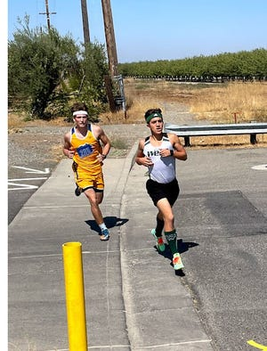 Ryan Mitchell of Weed High School, right, came in first place at a XC meet in Orland on Friday, Sept.  17, 2021.  He was followed in second place by Mount Shasta High runner Drew Hering, left,