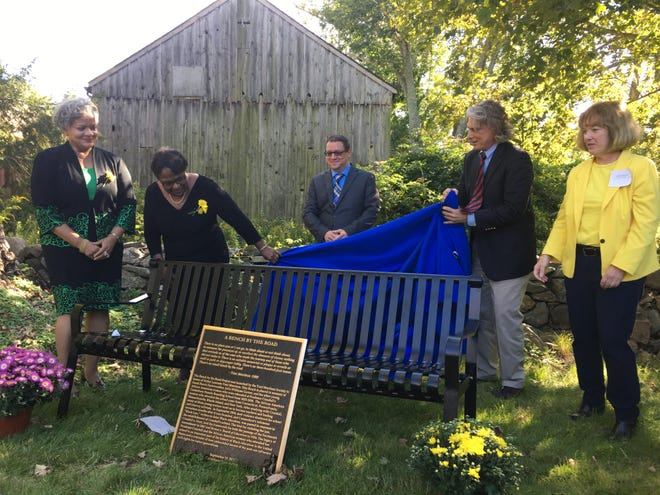 """Toni Morrison Society member Cheryl Gooch, society founder Carolyn Denard, society Chairman Craig Stutman, Canterbury First Selectman Chris Lippke and Windham Judicial District State's Attorney Anne Mahoney unveil the newest Toni Morrison """"Bench by the Road"""" at the Prudence Crandall Museum on Sunday in Canterbury."""