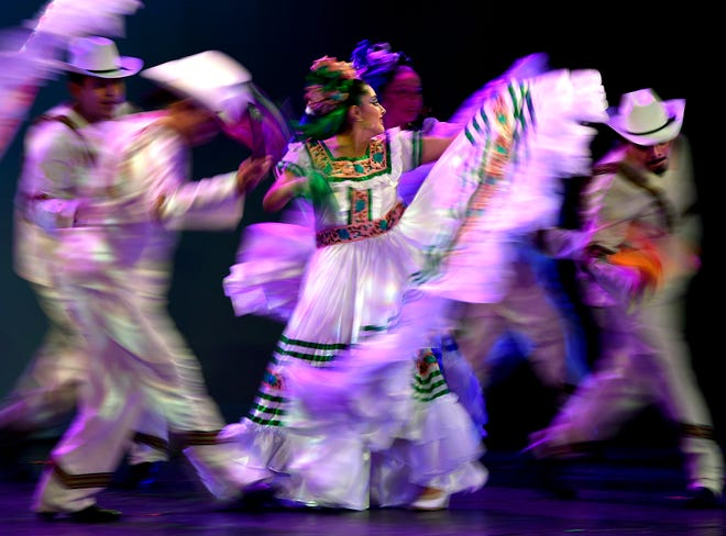 """Members of the St. Vincent Pallotti Catholic Church Ballet Folklorico are blurred in this slow exposure as they perform """"Mi Tierra Mexicana"""" Aug. 21. The Paramount Theatre performance featured dance performances from five regions in Mexico."""