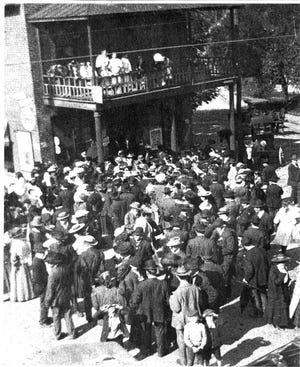 Women, on the balcony, attempt to convince male voters to support Prohibition during the 1907 campaign in Asheville. The photo depicts the polling place at Chedester's Grocery at 150 N. Main St., now Biltmore Avenue.