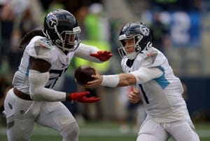 Tennessee Titans quarterback Ryan Tannehill, right, hands off to running back Derrick Henry during the second half of an NFL football game against the Seattle Seahawks, Sunday, Sept. 19, 2021, in Seattle.