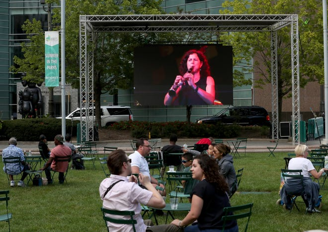 Jazz lovers gathered at Campus Martius to listen to the Jazz Fest via live stream to an out door screen Sunday, September 05, 2021. Clarinetist Anat Cohen plays onscreen.