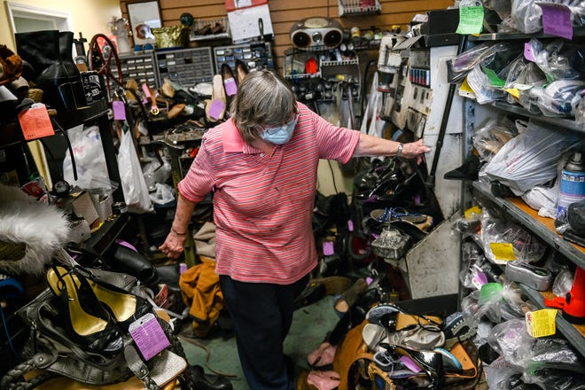 Co-owner of P and S Shoe Repair Susan Anderson, 76, looks at the shelves of unclaimed shoes on Monday, Sept. 20, 2021, at her store in Lansing. Unclaimed shoes must be held for at least three years before being donated or trashed but a new bill would shorten that period to 6 months.
