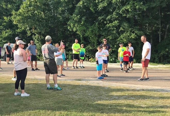 Kiwanis Club of Pike Road member Hardy Sellers, far right, and Pike Road Mayor Gordon Stone, at left in American flag T-shirt, talk to runners before the start of the Pike Road Family Fun Run at SweetCreek Farm Market.  The event, organized by the Kiwanis Club of Pike Road, generated $4,000 for libraries at Pike Road public schools.