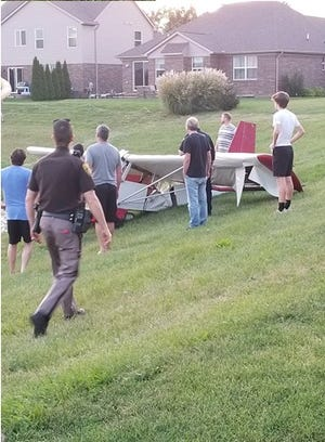 Residents living near this Lyon Township pond helped a Livonia pilot retrieve his ultralight glider plane from the water.