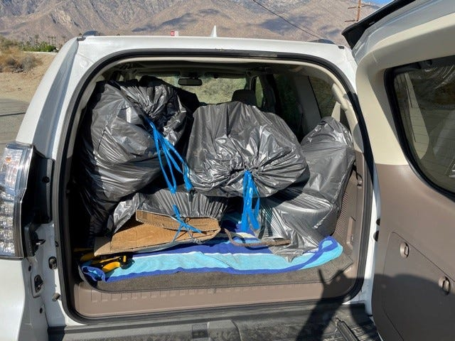 Two Palm Springs volunteers loaded bags full of trash from Palm Springs' Araby Wash as part of a statewide cleanup on Saturday.