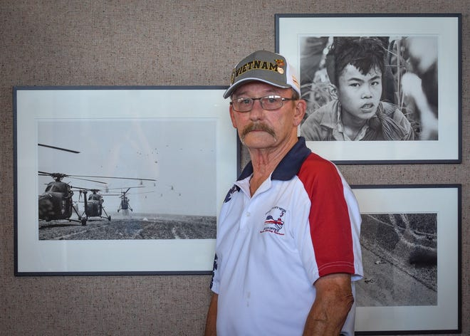 Fifty years ago this month, Ron Distel returned from serving in the Vietnam War to encounter disrespect and ingratitude. Here, he stands with of some of Eddie Adam's photos depicting the experiences of the Vietnam War soldier.